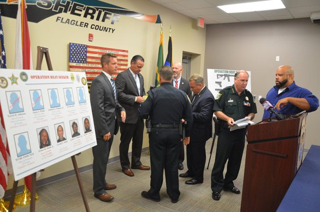 Sheriff Rick Staly, second from left, speaking with News-Journal reporter Matt Bruce after this morning's press conference. Behind him were State Attorney R.J. Larizza, immediately to Staly's left, Bunnell Police Chief Tom Foster, and federal officials. (© FlaglerLive)