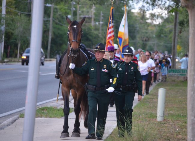 Sheriff Rick Staly, with a riderless horse symbolizing the loss of fallen officers, leads a procession from the county courthouse to the Sheriff's Operations Center ahead of a ceremony Thursday evening. Click on the image for larger view. (© FlaglerLive)