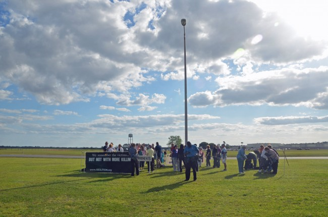Protesters, including, for the first time, a group from Flagler County, getting set for a prayer service and vigil before the execution of Larry Eugene Mann at Starke state prison, in the background. Click on the image for larger view. (© FlaglerLive)