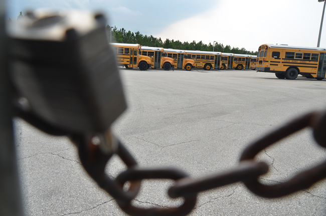 The thieves simply broke the lock on the gate at the bus depot, behind Flagler Palm Coast High School, drove in, and drove out with two buses. (© FlaglerLive)