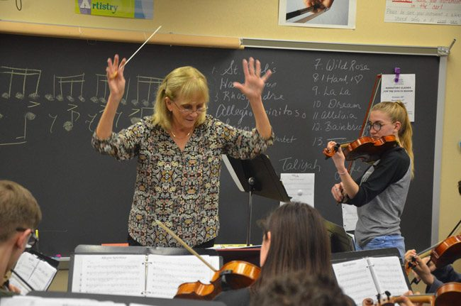 Flagler Youth Orchestra Artistic Director and Conductor Sue Cryan during Wednesday's rehearsal for the FYO's top orchestra's performance on Saturday, with Evan Hernandez, right, the concertmaster, performing a baroque duet. (© FlaglerLive)