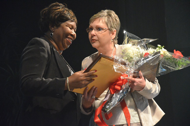 A somewhat surprised Sue McVeigh, right, accepting the Employee of the Year award from Harriett Holiday at the Flagler School Board's ceremony in January. (© FlaglerLive)