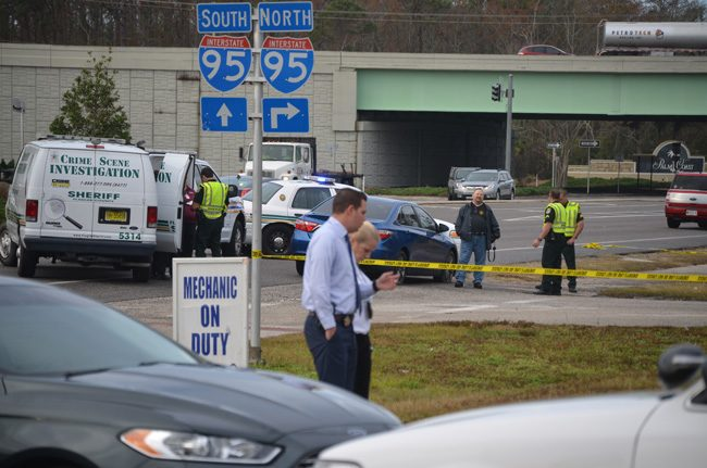 Investigators at the scene this morning. The apparent suicide took place in the blue car just before the intersection with I-95, on State Road 100. (c FlaglerLive)