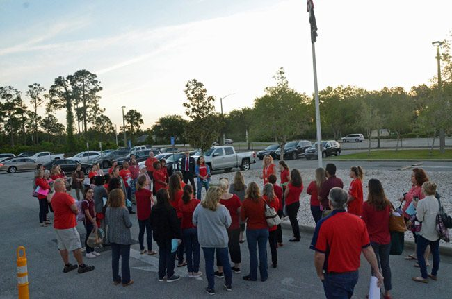 Just before sun-up at Indian Trails Middle School, walk-in participants, including teachers, administrators service employees and students, gathered at the flagpole, as they would at all nine of the county's traditional public schools this morning. (© FlaglerLive)