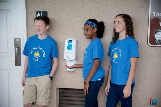 Last week Bunnell Futiure Problem Solvers Ryan Gilvary (left, DeErra Jones, and Aliyah Acevedo installed sunscreen dispensers at Bings Landing and Wadsworth Park. The group presented the idea to the County Commission on March 4. (Flagler Schools)