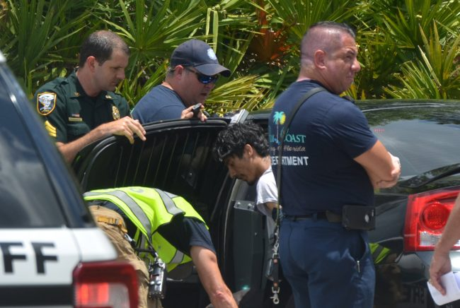 Levi Evan Ovenshire, the 19-year-old suspect, in the center of the picture, as he was being checked out by paramedics soon after his arrest on Rae Drive this afternoon. Click on the image for larger view. (© FlaglerLive)