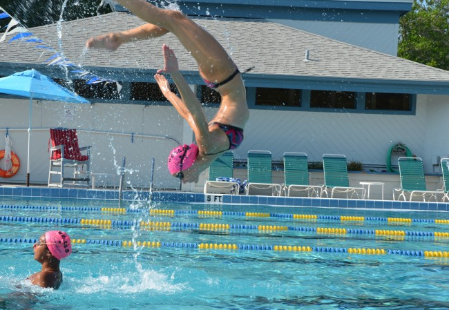 The Flagler County Synchro Belles' Carrie Hartnett flips out in a maneuver she executes with Alexis Solomon. Click on the image for larger view. (© FlaglerLive)