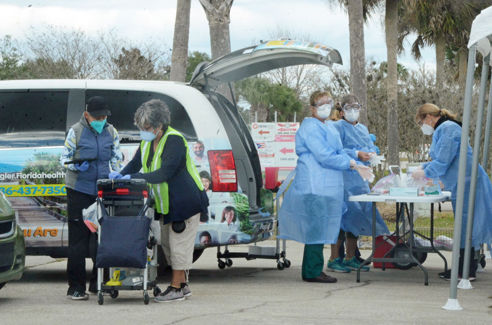 Flagler County Health Department staff providing Covid-19 testing to 100 people at the Flagler County Airport grounds this afternoon. See next week's testing schedule below the story. (© FlaglerLive)