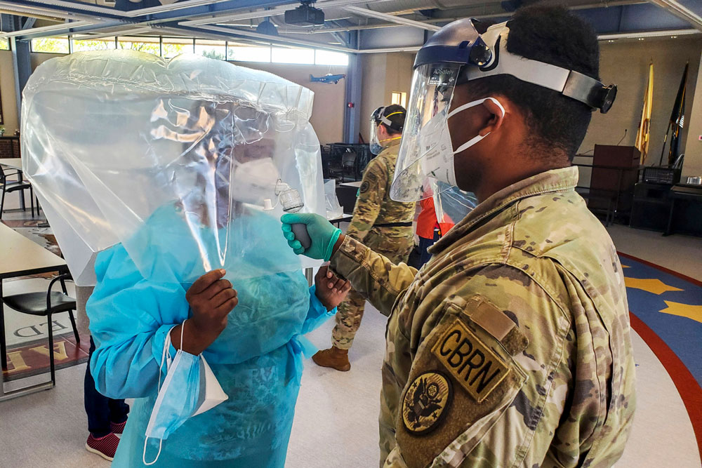 """Army Sgt. Quran Williams of the New Jersey National Guard administers a """"fit test"""" to a staff member at the New Jersey Veterans Home at Paramus in Paramus, N.J., April 16, 2020. The test of the N95 mask was conducted by using a sodium saccharin scent; staff members ensured they could not smell the scent through the mask when worn properly. (Zachary Vucic)"""