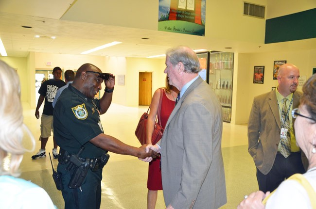 Then Sen. John Thrasher--now president of Florida State University--shaking hands with Calvin Grant, the school resource deputy, at Flagler Palm Coast High School during a visit in 2012, with Jacob Oliva, now the superintendent, behind Thrasher. (© FlaglerLive)