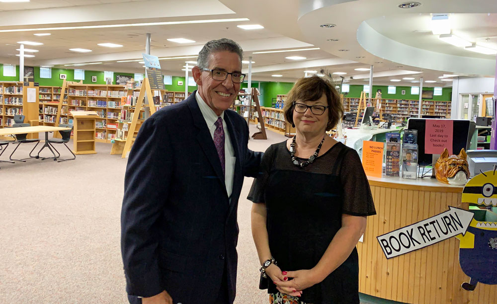 """Flagler Palm Coast High School Principal Tom Russell with his wife Julie at the school in June 2019, shortly after his appointment. """"It has shocked my family because of my vigilance about practicing safeguards,"""" he wrote of his Covid-19 diagnosis. (© FlaglerLive)"""
