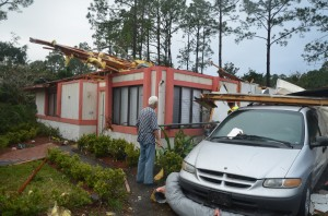 John Coberly, 77, surveys his house, which may be the most demolished of those struck by Sunday's tornado. Click on the image for larger view. (© FlaglerLive)
