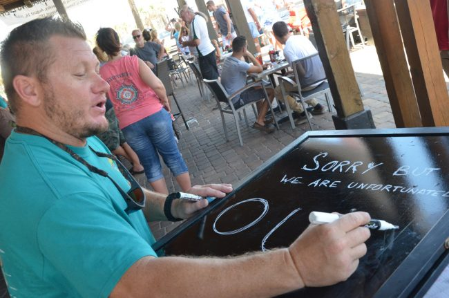 Tortugas owner Scott Fox had been giving away free eclipse glasses, but they went fast and he had to write out a sign that he'd run out: the party drew teeming patrons, however. Click on the image for larger view. (© FlaglerLive)
