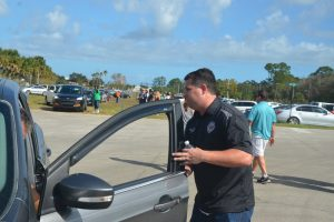 Sen. Travis Hutson provided traffic control as some 300 cars lined up at the Farm Share event this morning. Click on the image for larger view. (© FlaglerLive)