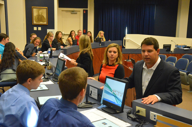 Rep. Travis Hutson, right, conferred with students Wednesday morning in Bunnell just before the mock legislative session that led to an actual bill Hutson will file at the Legislature ahead of this spring's session. (c FlaglerLive)