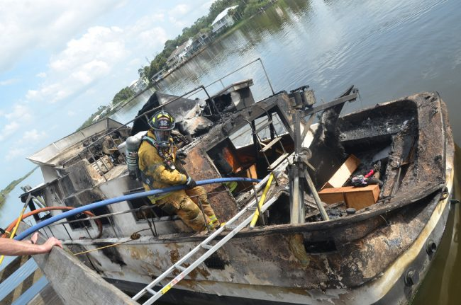 The trawler had started its journey in DeLand. It began smoking near the Flagler Beach bridge, where its pilot docked it and got off as the flames went out of control. Two hours later the boat was totaled. Click on the image for larger view. (© FlaglerLive)