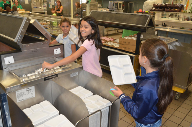 2nd graders at Old Kings boycotted the use of plastic trays on the way to convincing the administration to adopt more eco-friendly, biodegradable paperboard trays that don;t harm oceans, as plastics do. Today marked the first day of the trays' use county-wide. (© FlaglerLive)
