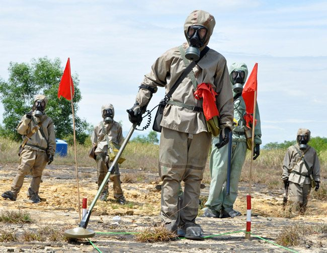 A Vietnamese soldier demonstrates unexploded-ordnance  detection and clearance in Danang in June 2011. Since 1975, The New Yorker reporter, more than 40,000 Vietnamese have been killed by unexploded ordnance many of them in Quang Tri, a province that was also 'sprayed with more than seven hundred thousand gallons of herbicide, mainly Agent Orange.' (USAID)