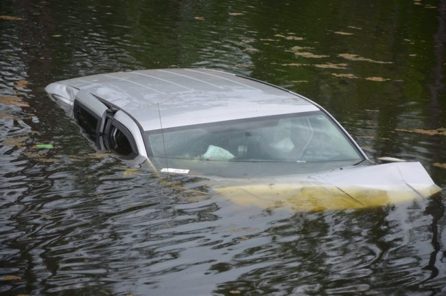One of the two vehicles, with a mom and two children on board, ended up in the pond by an access road near Palm Coast Parkway. Click on the image for larger view. (c FlaglerLive)