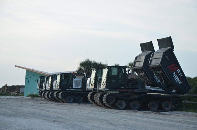 The line-up of dune-rebuilding and dumping machines at Varn Park along A1A, as the rebuilding continues. (© FlaglerLive)