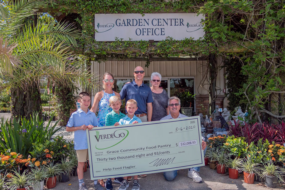 TJ McNitt, president and owner of Verdego, with his family and with Pastor Charles Silano, right, with the ceremonial $32,000 check. (Verdego)