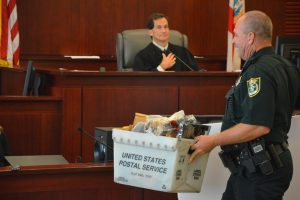 A bailiff takes the bin of evidence to the jury room for deliberations. Deliberations lasted less than half an hour, and little evidence was sought. (© FlaglerLive)