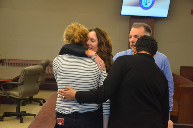 Assistant State Attorney Melissa Clark, hugs the victim after the verdict, with Sheriff's Detective Dennis Lashbrook, who investigated the case, and the State Attorney's victim's advocate. (© FlaglerLive)