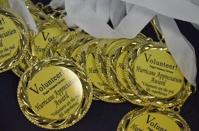 Some of the appreciation medals Flagler Volunteer Services handed out to its volunteers at a four-hour thank you event Wednesday at the County Fairgrounds. No fewer than 1,130 volunteers were documented to have lent a hand during the Hurricane Irma emergency. 'We know there's a lot more than that,' says Suzie Gamblain, who leads the organization. They helped at the Emergency Operations Center's call center, in all hurricane shelters, at the special assistance centers set up in the aftermath of the storm, they helped clean up people's homes, tarp roofs and do innumerable other jobs, for nothing in return. 'We couldn't have done the hurricane things we've done without you guys,' County Administrator Craig Coffey told the group. 'I just feel blessed to have each and every one of you.' (© FlaglerLive)