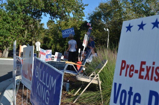 Campaign volunteers amid a small forest of signs at the Palm Coast Community Center this afternoon. (© FlaglerLive)