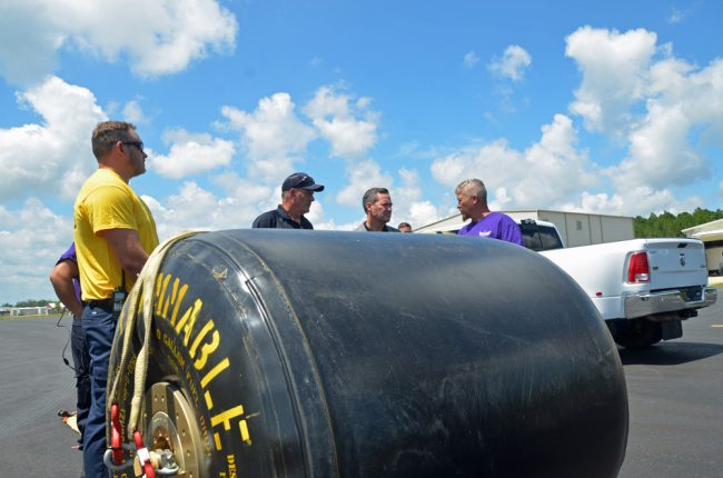 U.S. Rep Mike Waltz, second from right, behind a 500-gallon fuel blivet just ahead of a demonstration at the Flagler County airport last Thursday by the staff of Kimble's Aviation Logistical Services, which operates out of the airport and is set to provide logistical support in any area impacted by the hurricane. (© FlaglerLive)