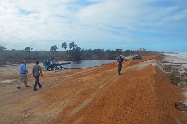 No dunes left, no coquina boulders, no dune vegetation, no walkway, no parking lot: Washington oaks Garden State Park's beach-side is a run, as state and county workers built an artificial barrier of packed sand and pumped water out of the parking lot to prevent another flood.