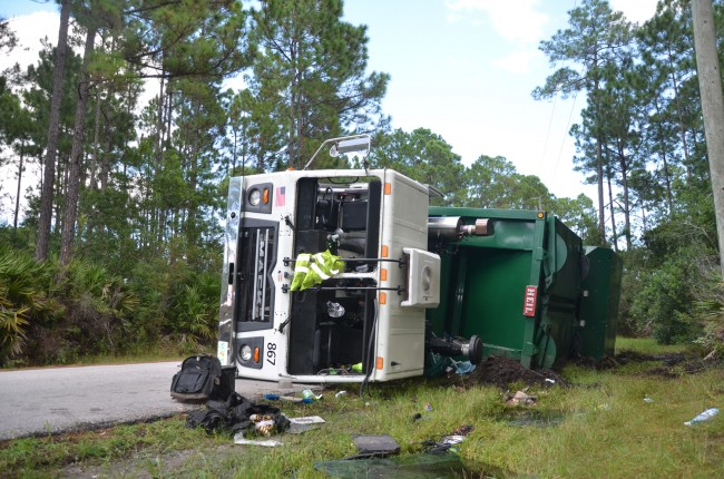 The Waste Pro  turck overturned as if was driving around the bend on Reybury Lane in Palm Coast. Click on the image for larger view. (c FlaglerLive)