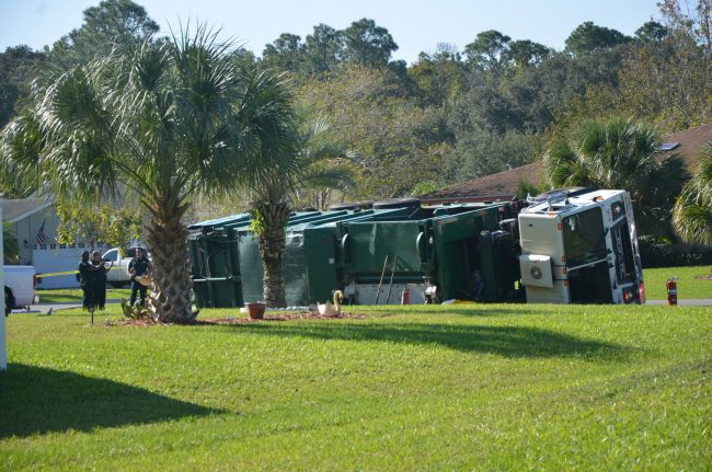 The Waste Pro garbage truck overturned in front of 1 Bay Spring Place in Palm Coast's Woodlands this morning, killing a man. (c FlaglerLive)