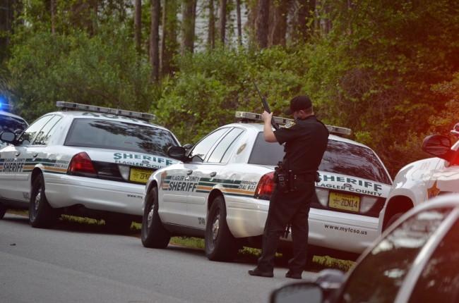 A Flagler County Sheriff's deputy examines one of the rifles seized on the incident on Utah Place. Click on the image for larger view. (© FlaglerLive)