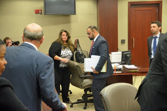 Kimberle Weeks and her lawyers, Kendell Ali, center, and Dean Bartzokis, to the right, were none too happy at the end of a hearing today when the prosecution questioned whether Weeks had standing to challenge a search warrant's validity. To the left of Weeks, walking away, is County Attorney Al Hadeed, toward whom Weeks has historically reserved particular animosity. (© FlaglerLive)