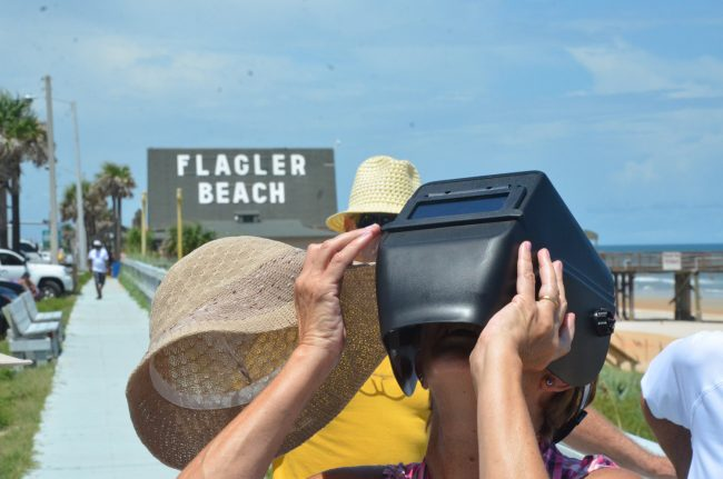 Linda Nugent, a 65-year-old Flagler Beach resident who was adamant that she'd not miss the eclipse--as she had opne in 1979--tried a welder's mask. Click on the image for larger view. (© FlaglerLive)