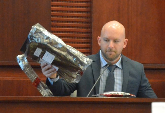 Former Florida Department of Law Enforcement Special Agent Clifford Whiteside, who testified for several hours today, with Paul Dykes's laptop, on which much of the incriminating evidence was found. Click on the image for larger view. (© FlaglerLive)