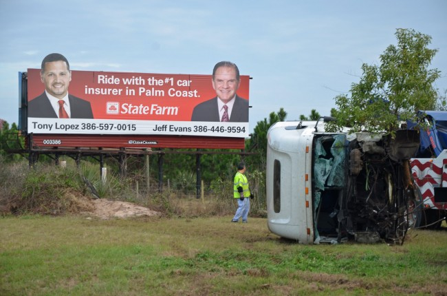 The cab portion of the semi truck just after it was fished out of a pond at the bottom of a 30-foot ravine, below the billboard. And no, State Farms is not an advertiser. Click on the image for larger view. (© FlaglerLive)