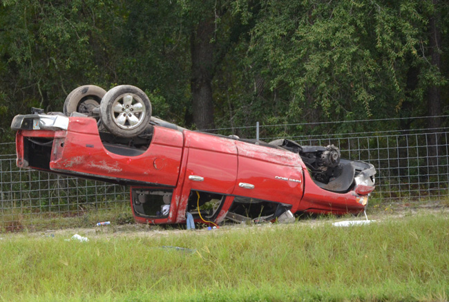 The Dodge Ram flipped and came to rest against a fence near Mile Marker 297 on I-95 this morning. (c FlaglerLive)