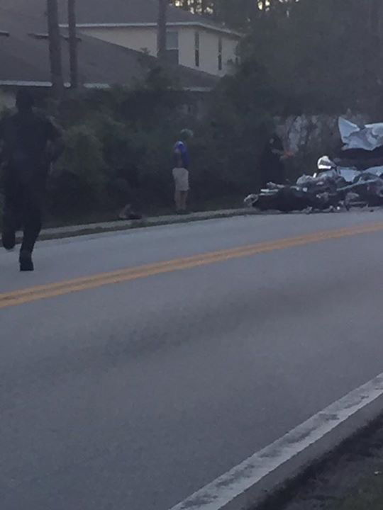 A Flagler County Sheriff's deputy runs to the scene immediately after the wreck this evening. (c FlaglerLive)
