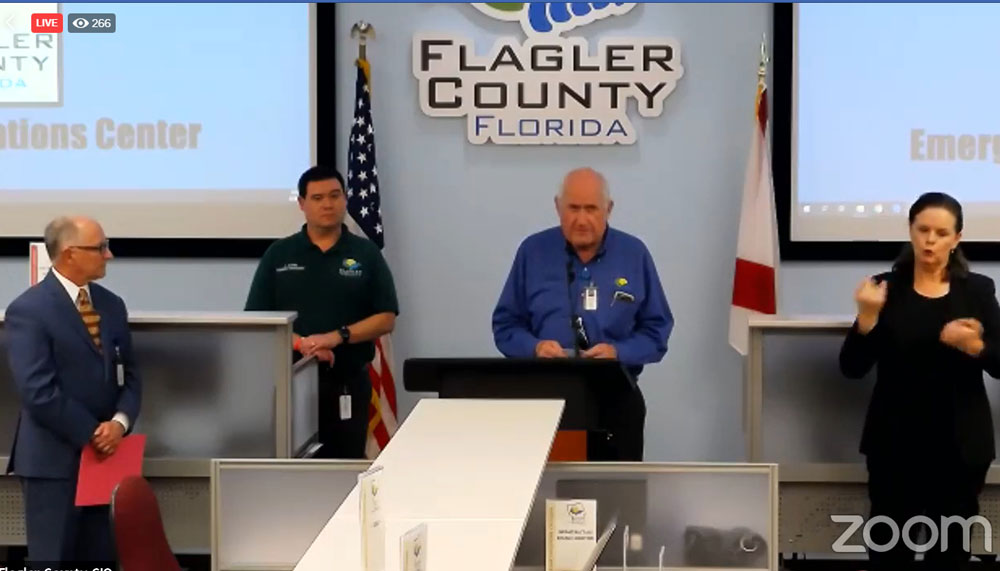 County Commission Chairman Dave Sullivan speaking today at the county's virtual press conference from the Emergency Operations Center, with Emergency Chief Jonathan Lord and Health Department Chief Bob Snyder. The conference had an interpreter for the deaf. (© FlaglerLive via Zoom)